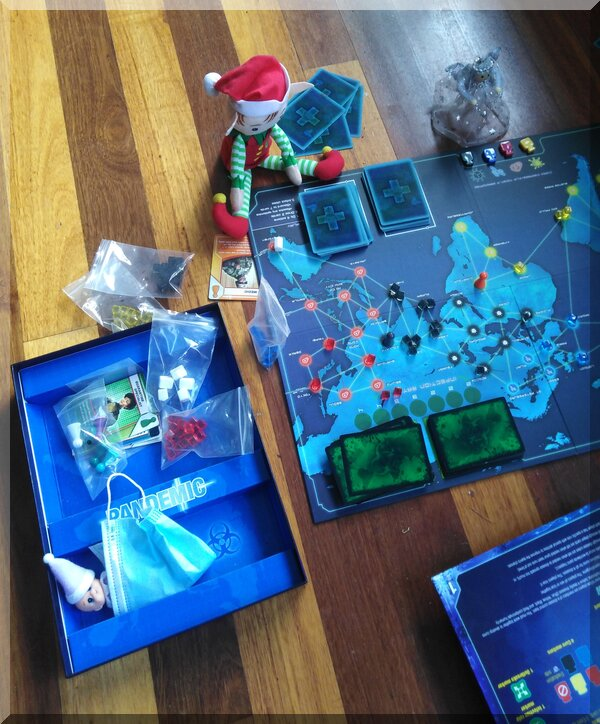 Christmas elf and angel playing the pandemic board game