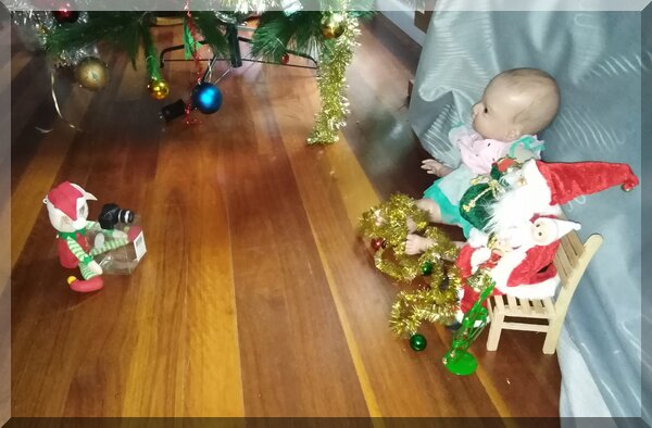 Christmas elf taking a photo of Santa with a bay elf and a large doll