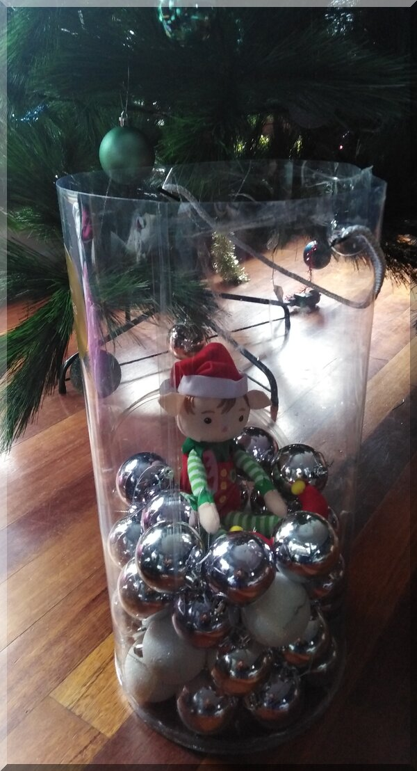 Christmas elf sitting in a bauble container